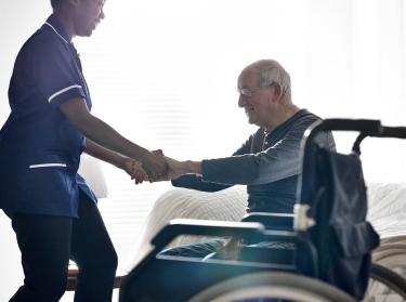 Nurse helping an elderly man out of a wheelchair