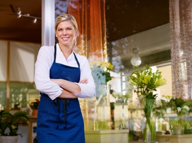 Female business owner standing in front of store