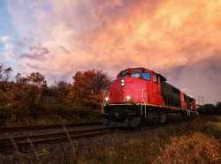 A freight train in a rural area with a sunset background