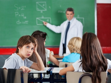 Portrait of young schoolboy leaning at desk with teacher teaching in background
