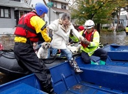 Emergency personnel help a resident onto a boat after rescuing her from flood waters brought on by Hurricane Sandy in Little Ferry, New Jersey, October 30, 2012, photo by Adam Hunger/Reuters