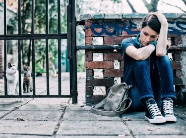 Adolescent girl sitting on sidewalk