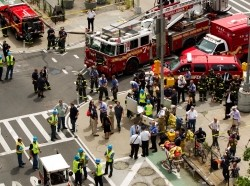Emergency services personnel inspect the site where part of a five-story building collapsed after a reported explosion in New York