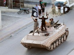 Militant Islamist fighters wave the ISIS flag atop a tank on the streets of northern Raqqa province, Syria, June 30, 2014, photo by Stringer/Reuters