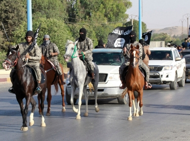 Militant Islamist fighters ride horses in a military parade along the streets of Syria's northern Raqqa province, June 30, 2014