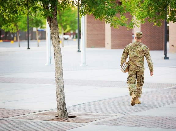 A soldier walks on a college campus