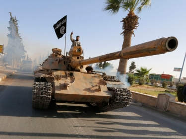 Militant Islamist fighters on a tank take part in a military parade along the streets of northern Raqqa province, Syria, June 3