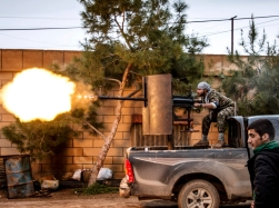 A fighter of the Kurdish People's Protection Units fires an anti-aircraft weapon at Islamic State fighters in Tel Tamer, Syria, February 25, 2015