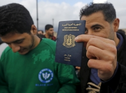 A Syrian refugee shows his passport after he and others were rescued by a Greek coast guard patrol boat, May 29, 2015