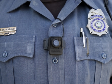A police officer poses with a body-worn camera on his chest in Colorado S