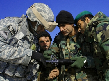 U.S. Army Capt. Kevin Mercer watches an Afghan National Army trainer adjust the sight on an M-16 rifle in Kandahar, Afghanistan, January 23, 2008