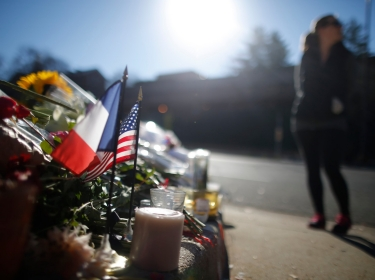 A passerby pauses near a makeshift memorial with U.S. and French flags outside the Frenc