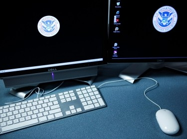 The logos of the U.S. Department of Homeland Security are seen on computer terminals