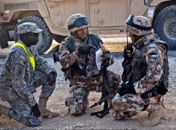 Jordanian soldiers discuss battle strategies while a U.S. Soldier, left, stands by in case an interpreter is needed
