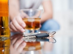 Car keys on the table while someone is drinking