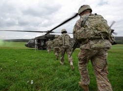 U.S. Army soldiers board a UH-60 Black Hawk helicopter at the Joint Multinational Training Command's Grafenwoehr Training Area in Germany, August 13, 2013