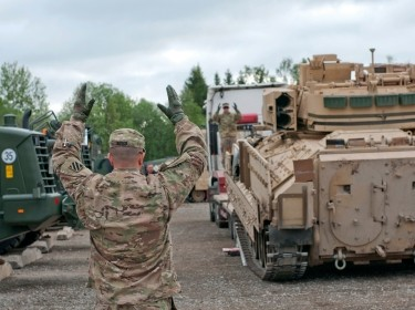 U.S. Army sergeant helps direct an M2A3 Bradley Fighting Vehicle off a flatbed on Tapa Army Base, Estonia, June 4, 2015