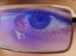 Russian President Vladimir Putin is reflected in the glasses of a cadet watching Putin on TV at a military school outside Rostov-on-Don, Russia, December 20, 2012