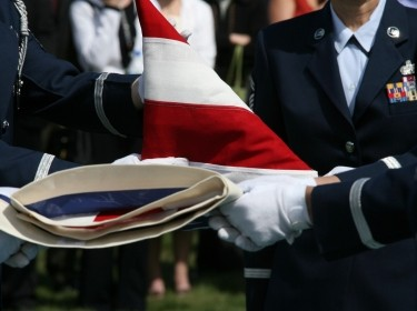 U.S. military personnel fold the American flag at a funeral