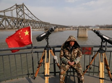 A man sits between binoculars that he offers to tourists to watch the North Korean side of the Yalu River in Dandong, China, April 1, 2017