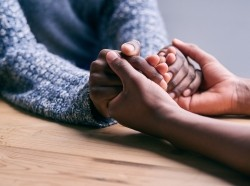 Two people holding hands in a comforting manner