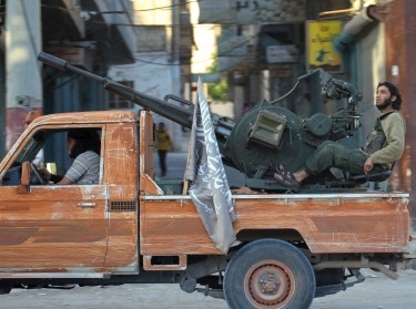 Members of al Qaeda's Nusra Front ride on a pickup truck mounted with an anti-aircraft weapon in Ariha, Syria, May 29, 2015