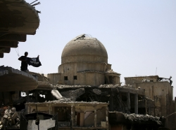 A member of Iraqi security forces holds an Islamic State flag on top of a destroyed building in Mosul
