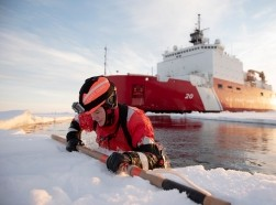 U.S. Coast Guard Petty Officer 3rd Class Shannon Eubanks pulls herself out from the Arctic Ocean during ice rescue training Oct. 3, 2018, about 715 miles north of Barrow, Alaska, photo by Senior Chief Petty Officer NyxoL/U.S. Coast Guard