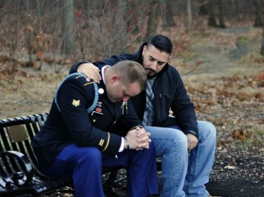 Friend comforts uniformed United States Army soldier sitting on park bench, photo by debbiehelbing/Getty Images