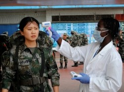 A Chinese military health worker, part of a delegation sent by China to help in the fight against Ebola, has her temperature taken as she arrives at Roberts airport outside Monrovia, November 15, 2014, photo by James Giahyue/Reuters