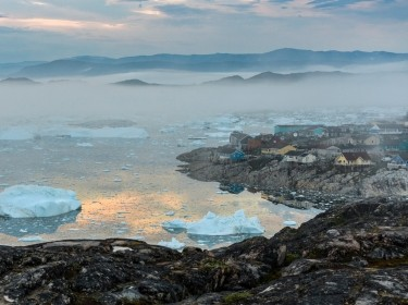 View from the end of the Ilulissat Icefjord to the town Ilulissat at the Disko Bay in western Greenland at midnight in July, photo by renelo/Getty Images
