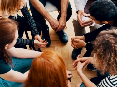 High angle of a group of teenagers sitting in a circle during group therapy for bullying victims, photo by KatarzynaBialasiewicz/Getty Images