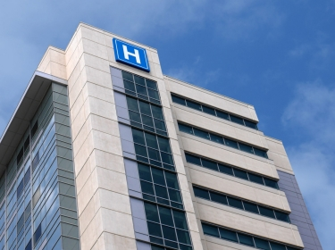 Building with large H sign for hospital, photo by peterspiro/Getty Images