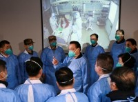 Chinese Premier Li Keqiang wears a mask and protective suit while speaking to medical workers at the Jinyintan hospital, where coronavirus patients are being treated following the outbreak in Wuhan, China, January 27, 2020, photo by cnsphoto via Reuters