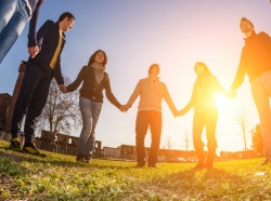 young people holding hands in a circle with the sun setting