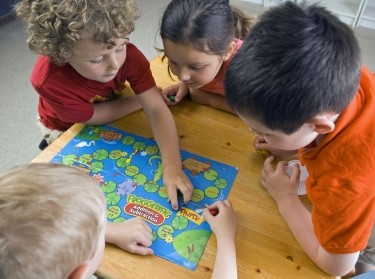 Children have fun and learn while playing a board-game at the preschool class