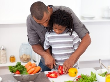 A father helps his son cut vegetables