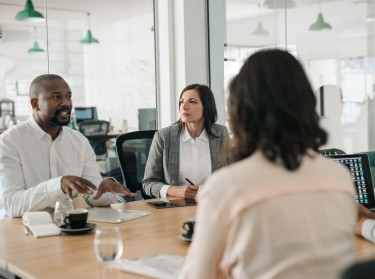 African American businessman talking with colleagues during an office meeting, photo by mavoimages/Adobe Stock