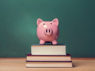 Piggy bank and school books in a classroom