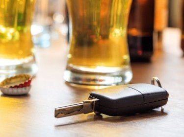 Car key on a wooden bar counter next to a glass of beer. Photo by Rawf8/Adobe Stock