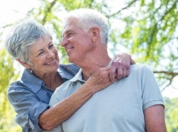 A happy older couple embraces and smiles