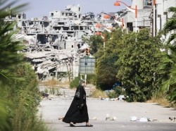 A woman walks near a residential area in the city of Homs destroyed in the fighting between the rebels of the Syrian National Army