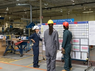 Three factory workers standing next to a message board in a factory