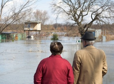 Older man and woman surveying flood damage