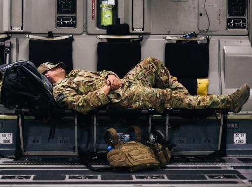 A U.S. Air Force Airman sleeps inside a C-17 Globemaster during a flight