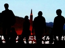 People walk in front of a monitor showing news of North Korea's fresh threat in Tokyo, Japan, August 10, 2017, photo by Toru Hanai/Reuters