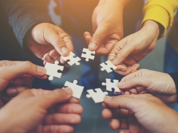 Group of hands in a circle, each holding a puzzle piece, photo by Patcharin Saenlakon/Getty Images