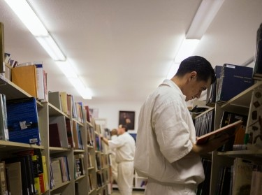 Inmates search for books at a library inside the Southwestern Baptist Theological Seminary located in the Darrington Unit of the Texas Department of Criminal Justice men's prison in Rosharon, Texas, August 12, 2014