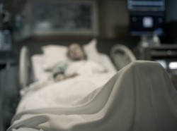 A person lying in a hospital bed covered by a sheet. Photo by kieferpix / Getty Images