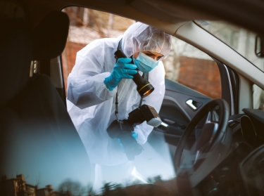 A police photographer investigating a crime scene. Photo by Milan Markovic / Getty Images